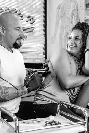 tattooing: knowing look between tattoo artist and a young female customer while is tattooing her back in the tattoo cabin at his tattoo shop - focus on the woman face