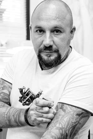 tattooing: portrait of a tattoo artist is tattooing his arm in the tattoo cabin at his tattoo shop - focus on the man face Stock Photo