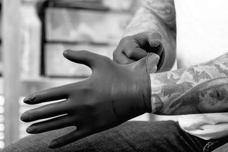 closeup of the hands of a tattoo artist putting on the latex gloves before a tattoo session at the tattoo shop - focus on the right forefinger