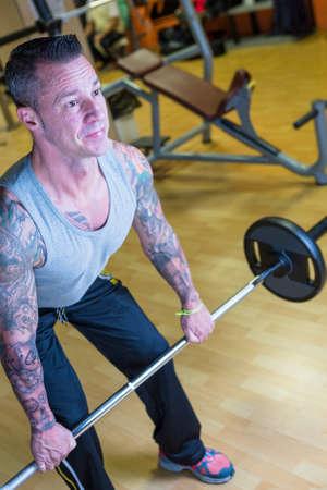 dorsal: hombre que hace inclin� sobre remo con barra - ejercicio dorsal - en el gimnasio - empezar ejercicio - se centran en la cara del hombre Foto de archivo