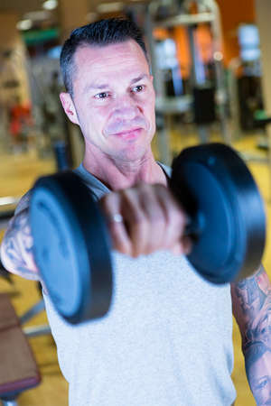 raises: closeup of a man making standing dumbbell front raises - shoulder exercise - at the gym - finish exercise - focus on the man face Stock Photo