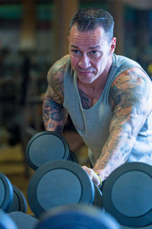 tricep: man making dumbbell kickback - tricep exercise - at the gym - start exercise - focus on the man face Stock Photo