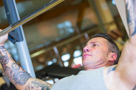 to incline: man making incline barbell bench press - chest exercise - at the gym - focus on the man face Stock Photo
