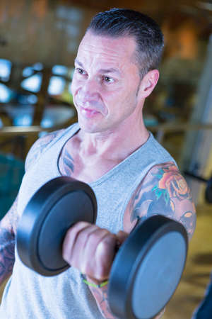 alternate: closeup of a man making standing dumbbell alternate curl - bicep exercise - at the gym - focus on the man face
