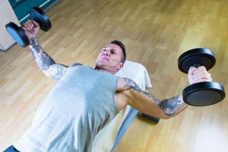 levantar pesas: hombre que hace mancuerna con mosca - ejercicio de pecho - tumbado en un banco en el gimnasio - empezar ejercicio - se centran en la cara del hombre Foto de archivo