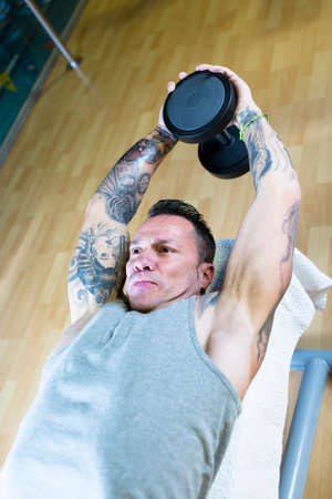 'pull over': young man making dumbbell pull overs - chest exercise - lying on a bench at the gym - start exercise - focus on the man face