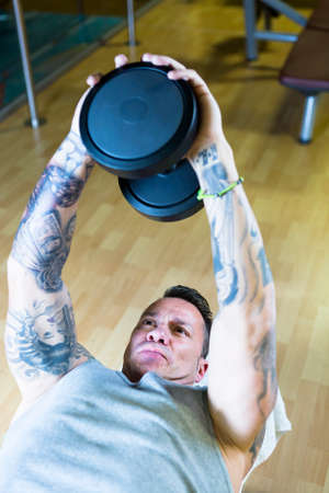 overs: young man making dumbbell pull overs - chest exercise - lying on a bench at the gym - finish exercise - focus on the man face