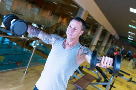 raises: young man making standing dumbbell lateral raises - shoulder exercise - at the gym - finish exercise - focus on the man face