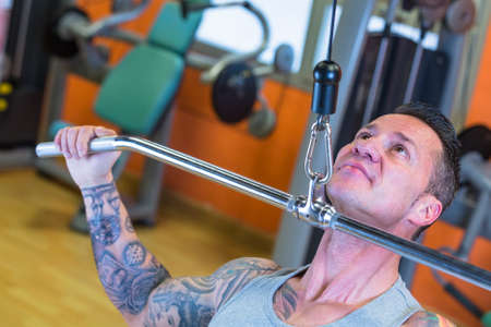 dorsal: closeup of a man making lateral pull downs seated - dorsal exercise - at the gym - finish exercise - focus on the man face Stock Photo