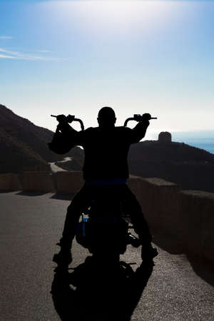 backlighting of a rear view of a biker man sitting on his chopper motorbike enjoying the view - focus on the head