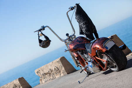 customized: customized chopper motorcycle with a helmet and a leather black jacket hanging on the handlebar over a sea and sky background at sunrise - focus on the helmet Stock Photo