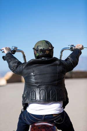 vista trasera de un motociclista que conducía su motocicleta chopper personalizada por una carretera de montaña al amanecer - se centran en la cabeza
