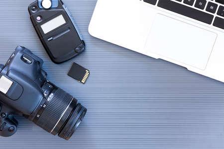 Draufsicht auf einen Desktop eines Fotografen aus einer Kamera, einem Laptop, einem Photometer und einer Speicherkarte auf einem grauen Hintergrund Schreibtisch - geeignet für Kopie Raum