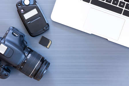 top view of a desktop of a photographer consisting on a camera, a laptop, a photometer and a memory card on a grey desk background - suitable for copy space