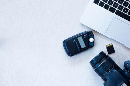 Draufsicht auf einen Desktop eines Fotografen aus über eine Kamera, ein Laptop, ein Photometer und eine Speicherkarte auf einem Schreibtisch-Hintergrund - geeignet für Kopie Raum