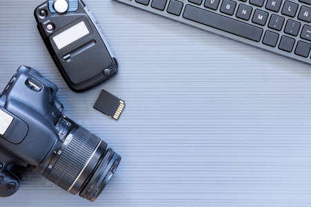 top view of a desktop of a photographer consisting on a camera, a keyboard, a photometer and a memory card on a grey desk background - suitable for copy space Stock Photo