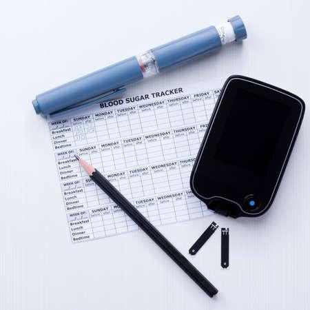 Draufsicht auf eine Diabetes-Kontrolle eingestellt Hintergrund, bestehend aus: einem Insulinpen, ein Blutzuckermessgerät, Teststreifen, ein Blutzuckertagebuch und einen Stift auf weißem Hintergrund