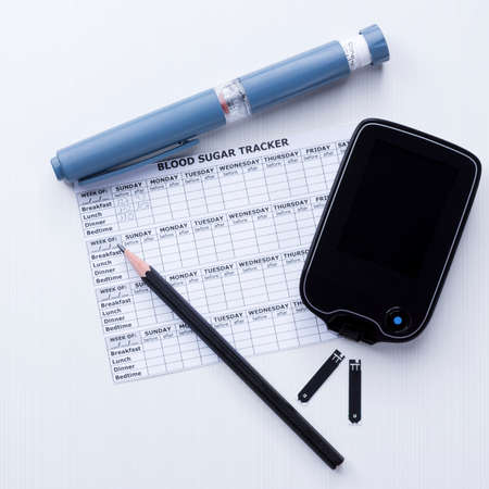 top view of a diabetes control set background consisting of: an insulin pen, a glucometer, test strips, a blood glucose diary and a pen on a white background