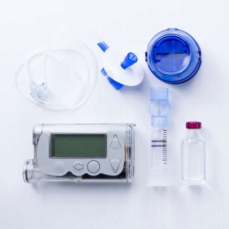 top view of an insulin pump set background consisting of: an insulin pump, insertion system of the infusion set, a reservoir of an insulin pump, insulin vial and a infusion set on a white background