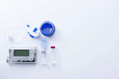 top view of an insulin pump set background consisting of: an insulin pump, insertion system of the infusion set, a reservoir of a insulin pump, insulin vial and a infusion set on a white background Stock Photo