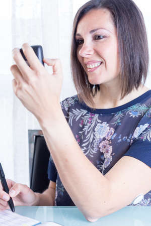variability: smiling young woman is looking at a reader after scanning the sensor of the glucose monitoring system ready to write the data on a blood glucose diary at home - focus on the woman left eye