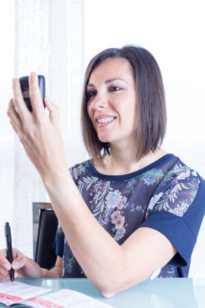 monitoring system: smiling young woman is looking at a reader after scanning the sensor of the glucose monitoring system ready to write the value on a blood glucose diary at home - focus on the woman right eye