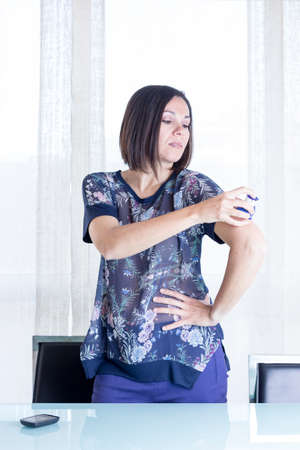 monitoring system: woman is applying the sensor of the glucose monitoring system at the back of her arm with the applicator at home - focus on the woman eye Stock Photo
