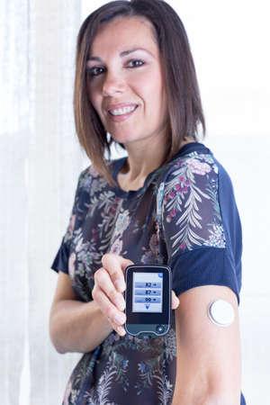 junge Frau, die den Leser nach dem Scannen des Sensors der Zuckermesssystem zu Hause - auf dem Lesegerät Standard-Bild