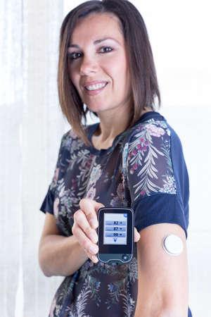 monitoring system: young woman is showing the reader after scanning the sensor of the glucose monitoring system at home - focus on the reader