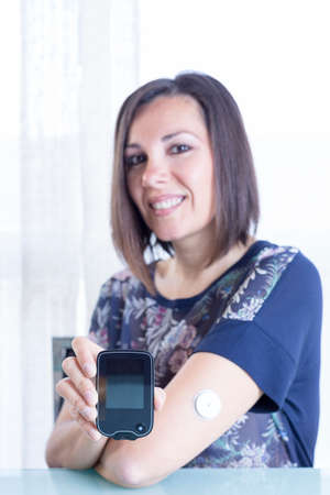 monitoring system: young woman is holding a reader after scanning the sensor of the glucose monitoring system at home - focus on the reader Stock Photo