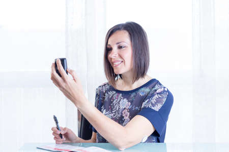 blood glucose: smiling young woman is looking at a reader after scanning the sensor of the glucose monitoring system ready to write the value on a blood glucose diary at home - focus on the woman face