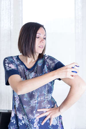 monitoring system: young woman is applying the sensor of the glucose monitoring system at the back of her arm with the applicator at home - focus on the woman eye