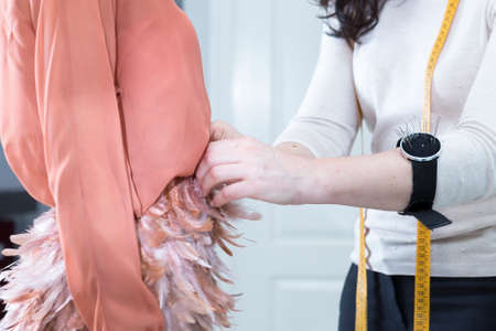 atelier: detail of the hands of a dressmaker is tweaking waist of the the dress of a female customer during a sewing session at her sewing atelier - focus on the dressmaker hand