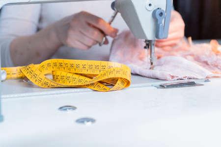 junge Schneiderin näht den Stoff an einer Nähmaschine in ihrer Näharbeit atelier sitzend - konzentrieren sich auf das Nähen Maßband
