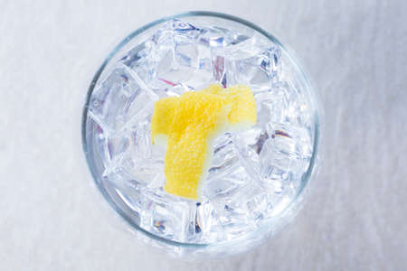 top view of a gin tonic balloon glass with lemon peels on it on a flavoring process on a gin tonic preparation session - focus on the lemon peel Imagens