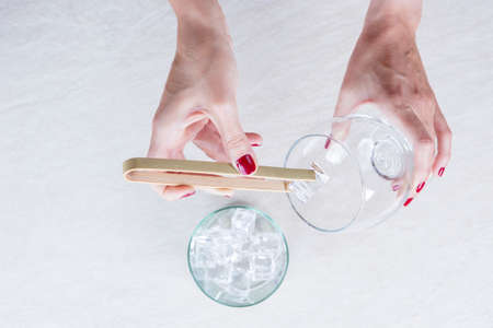 ice bucket: closeup of a woman hand filling a balloon glass with ice from an ice bucket with a bamboo ice tongs on a gin tonic preparation session - focus on the ice cube Stock Photo