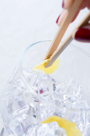 flavoring: detail of a hand of a woman flavoring inside a gin tonic balloon glass holding a lemon peel with bamboo ice tongs on a flavoring process on a gin tonic preparation session - focus on the lemon peel