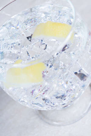 elaboration: closeup of a finished gin tonic balloon glass on a gin tonic preparation session - focus on the center of the image Stock Photo