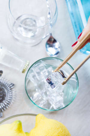 ice bucket: detail of a woman hand taking ice cubes from an ice bucket with a bamboo ice tongs on a gin tonic session - focus on the ice cube