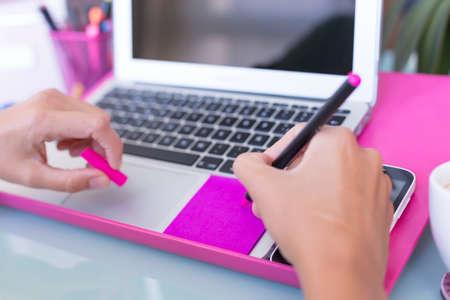 Nahaufnahme von der Hand einer Frau, die Noten auf einem farbigen Post es auf einem Schreibtisch - konzentrieren sich auf die Stiftspitze