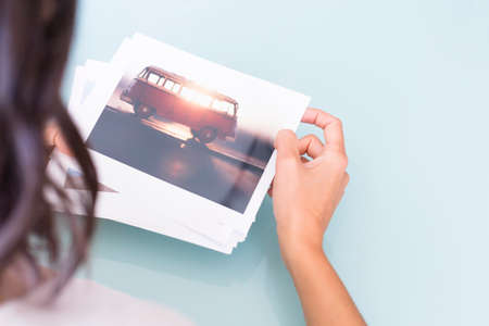 rear view of a woman holding a collection of photos on a selection process of images on a desk after a photoshoot - focus on the van