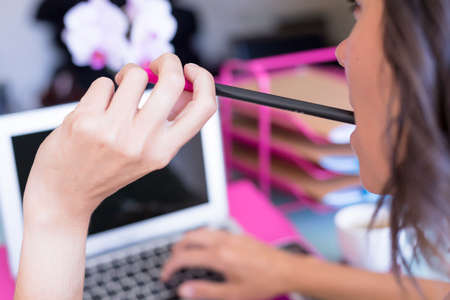 closeup of a woman holding a pen with the mouth while is working on a desk - focus on the mouth