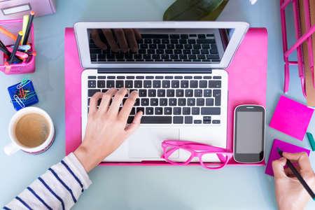 mecanografía: vista superior de una mujer que toma notas mientras que trabaja en un escritorio de trabajo - se centran en el teléfono móvil