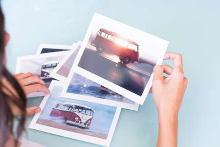rear view of a young woman holding a collection of photos on a selection process of images on a desk after a photoshoot - focus on the van Standard-Bild