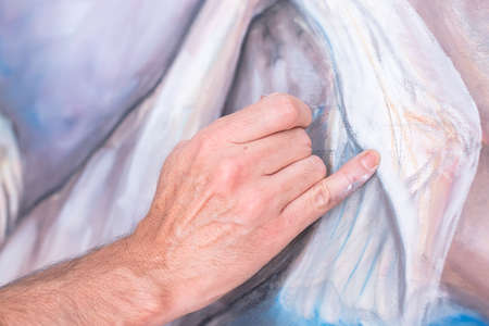 little finger: detail of the hand of a painter painting with chalk on canvas - focus on little finger Stock Photo