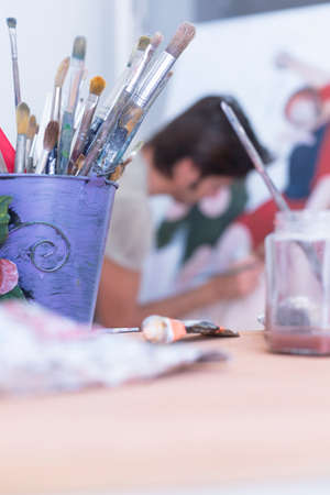 closeup of a container full of paintbrushes with a painter at background at his painting studio - focus on the paintbrush