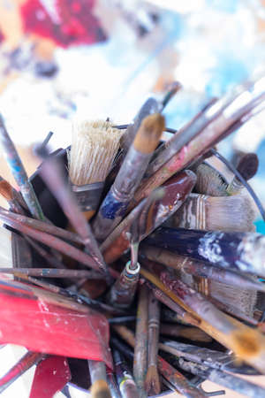 palette knife: top view of a container full of paintbrushes - focus on the palette knife