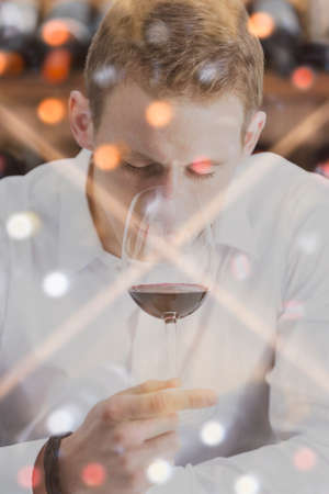 olfactory: double exposure of a man on a wine tasting session is smelling the wine with the wineglass in the nose and a wine rack background