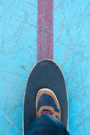 subjective: top view of a foot of a skater on a skateboard - focus on the shoe