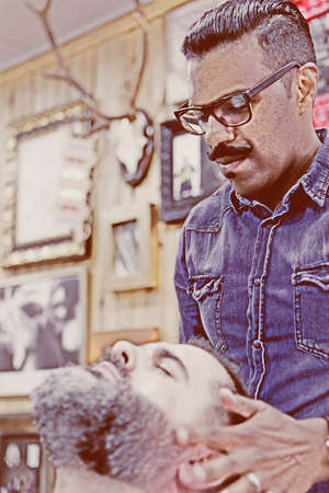 costumers: male barber is massaging the costumers beard on a beard shaving session in a barber shop - focus on the barber face